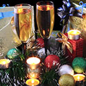 Two glasses of champagnes surrounded by holiday bulbs and garland.