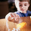 Photo of a young boy leaning over a table where a bottle of pills has been opened with contents spilled across the table.