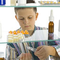 Young boy stands in front of open medicine cabinet looking at rows of medicine bottles.