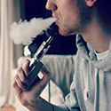 Photo of young man vaping, exhaling cloud of smoke.